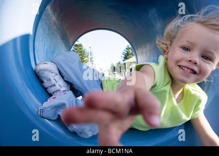Close-up of girl reaching for camera, lying in playground tunnel - Stock Photo