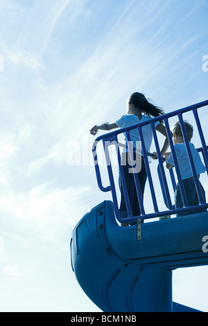 Children standing on playground slide, low angle view, rear view - Stock Photo