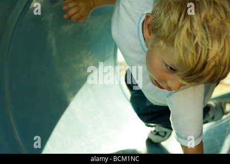 Boy on playground equipment, cropped, close-up - Stock Photo