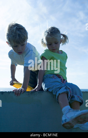 Boy and girl on wall, sky in background - Stock Photo
