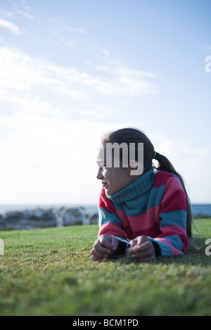 Girl lying on grass, looking away - Stock Photo