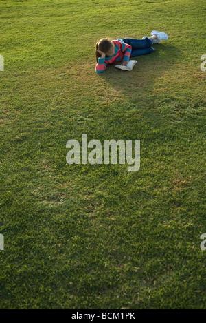 Girl lying on grass, reading book, full length - Stock Photo
