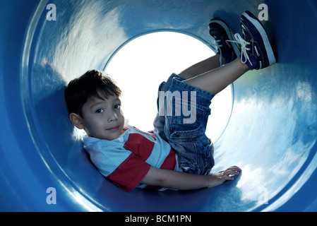 Boy sitting in playground tunnel with legs up, looking at camera, full length - Stock Photo