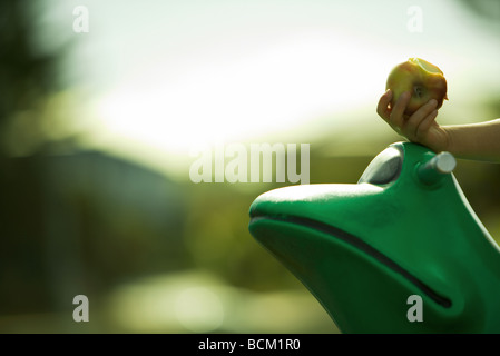 Child's hand holding apple, on top of frog shaped playground equipment, cropped - Stock Photo