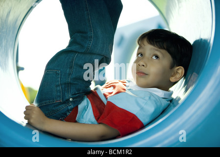 Boy lying in playground tunnel with legs up, looking up, close-up - Stock Photo