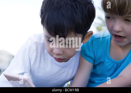 Children playing with handheld video game, close-up - Stock Photo