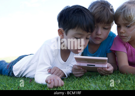 Three children lying on grass, playing with video game, close-up - Stock Photo