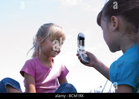 Girl taking picture of friend with cell phone, low angle view - Stock Photo