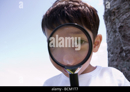 Boy looking through magnifying glass, close-up - Stock Photo