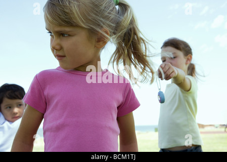 Three children outside, girl in foreground turning head while girl in background holds out toy to her - Stock Photo
