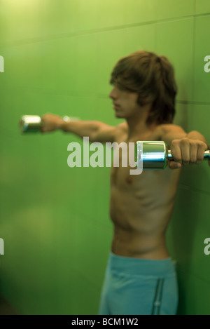 Young man holding dumbbells out to side, side view - Stock Photo