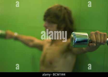 Young man holding dumbbells out to side, side view, focus on foreground - Stock Photo