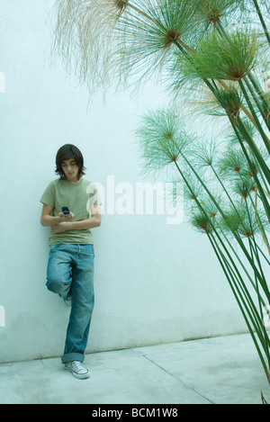 Teenage boy leaning against wall, using cell phone, full length - Stock Photo