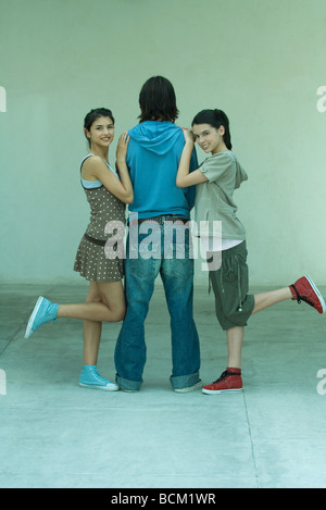Young females standing on either side of male friend, full length - Stock Photo