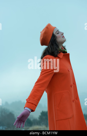 Teenage girl wearing coat and beret, standing outdoors with arms out, eyes closed, side view - Stock Photo
