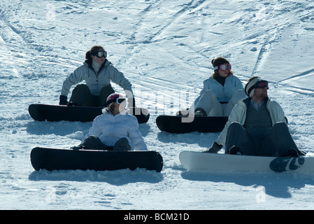 Four young snowboarders sitting on ski slope, looking away - Stock Photo