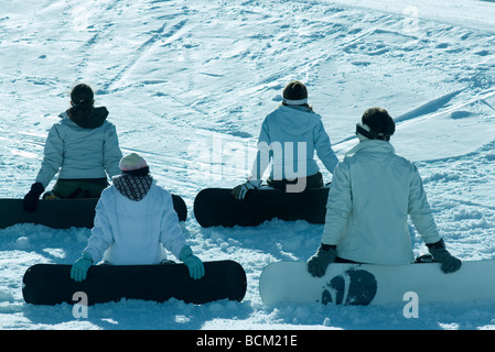 Four young snowboarders sitting on ski slope, rear view - Stock Photo