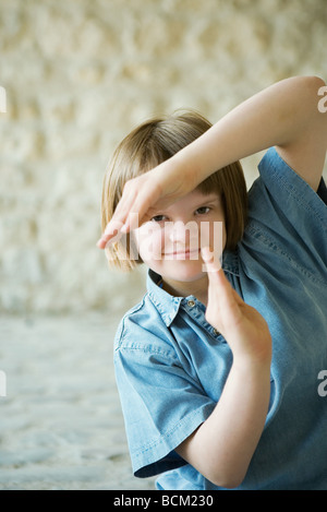 Girl with Down's Syndrome in martial arts pose, arms raised, smiling at camera, portrait - Stock Photo