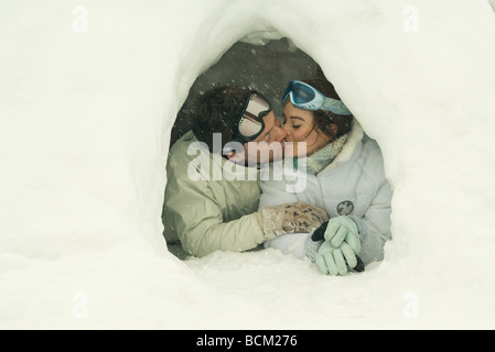 Young couple kissing in igloo, eyes closed Stock Photo