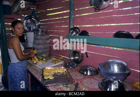 Woman cutting fresh fruits in a local kitchen. Caribbean - Dominican Republic Island - Stock Photo