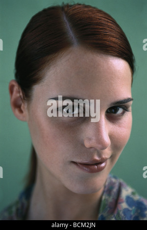 Young woman smirking at camera, portrait - Stock Photo