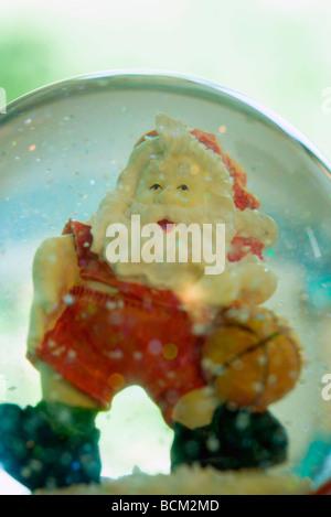 Santa Claus playing basketball in snow globe - Stock Photo