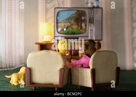 Plastic couple watching TV in miniature living room, rear view - Stock Photo
