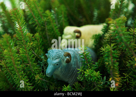 Toy rams walking through vegetation - Stock Photo