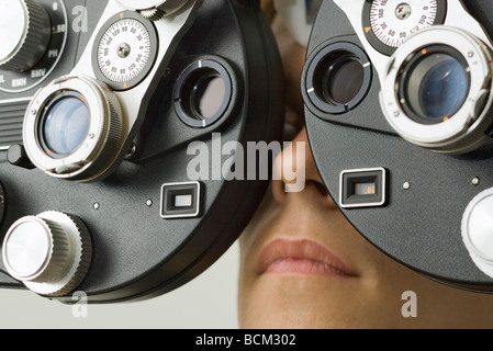 Patient looking into phoropter at eye doctor's office, extreme close-up - Stock Photo