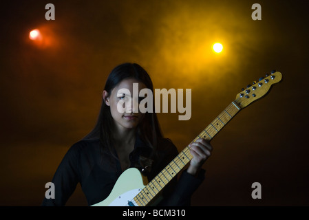 Female playing electric guitar in night club, looking at camera - Stock Photo