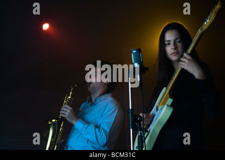 Young musicians playing electric guitar and saxophone in night club - Stock Photo