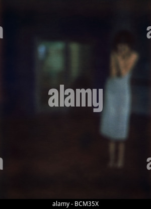 Woman standing in dark room with arms against chest, defocused - Stock Photo