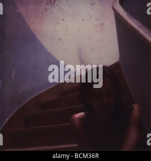 Young woman sitting in staircase - Stock Photo