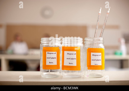 Glass bottles in classroom lab for disposal of Pipets - Stock Photo