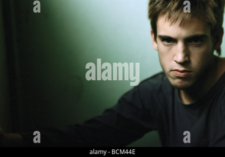 Young man with angry expression looking at camera - Stock Photo