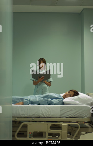 Woman lying on hospital bed, looking at camera, nurse looking at chart in background - Stock Photo