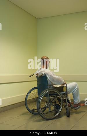 Man sitting in wheelchair in corner, facing wall - Stock Photo