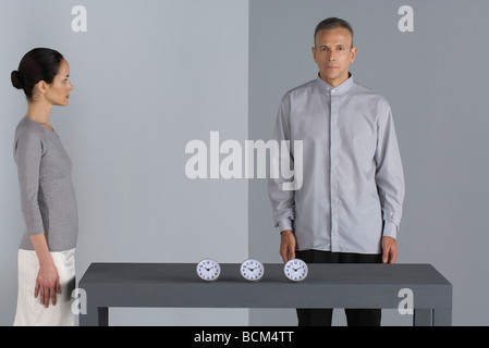 Man and woman standing by table with line of clocks, man looking at camera - Stock Photo