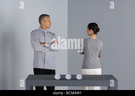 Couple standing with arms folded, looking at each other, clocks on table in front of them - Stock Photo