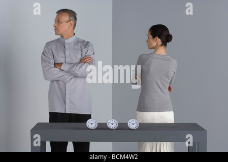 Couple standing with arms folded, backs turned to each other, clocks on table in front of them - Stock Photo