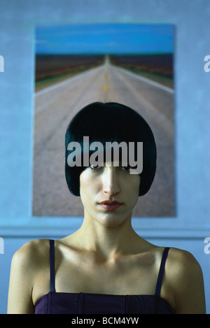 Woman staring at camera, portrait, painting of highway in background - Stock Photo