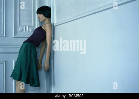 Woman leaning against wall in corner, low angle view - Stock Photo