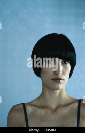 Woman with black hair looking at camera, portrait - Stock Photo
