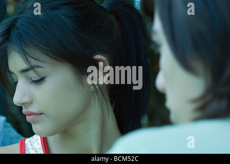 Young woman turning head away from teen boy, cropped view - Stock Photo