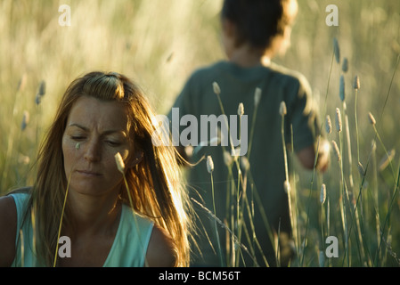Woman in field of tall grass, furrowing brow, son exploring in background - Stock Photo