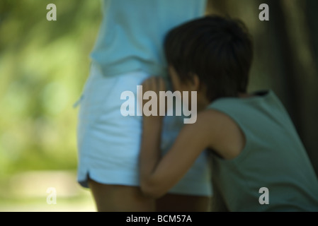Boy crying, leaning against mother, defocused - Stock Photo