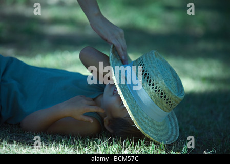Boy lying in grass, adult placing straw hat on face, cropped view - Stock Photo