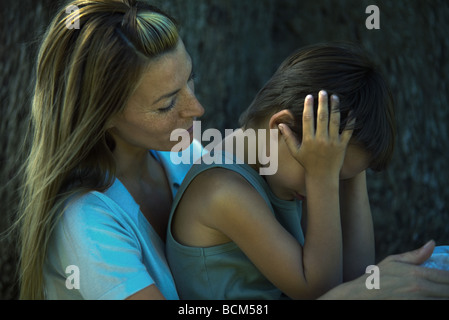 Mother consoling son, boy sitting on woman's lap and holding head - Stock Photo