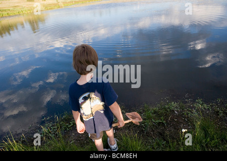 young boy looking into a lake with the sky reflected in the water - Stock Photo