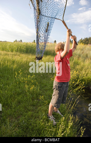 ten year old boy raising his net to show a crawfish he caught in a stream, southern Colorado, USA - Stock Photo